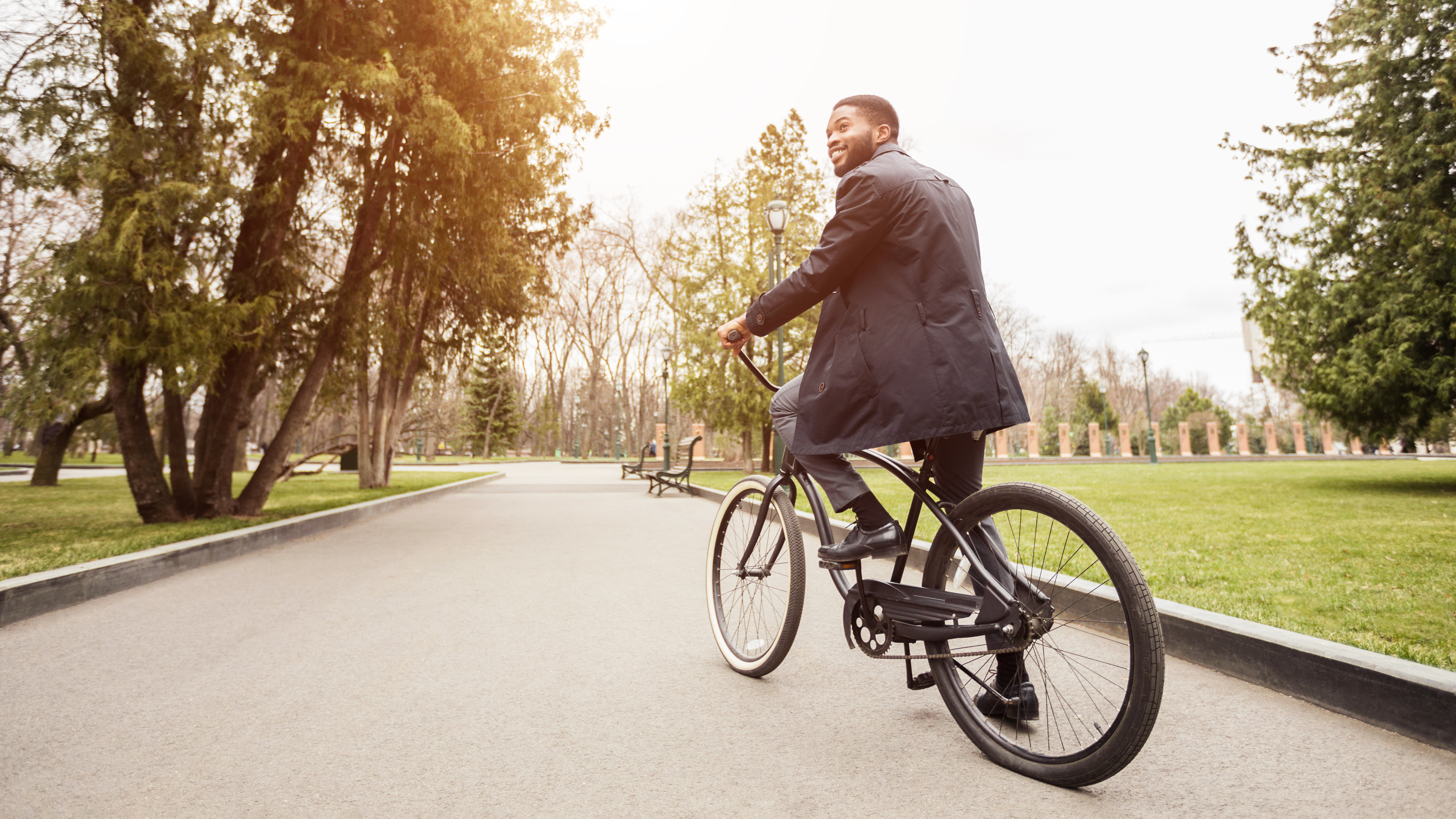 Gas savings concept. Young businessman riding bicycle to work